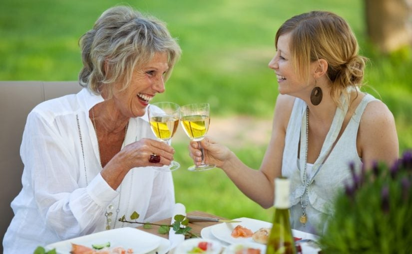 Svigermor og svigerdatter der hygger med mad og vin