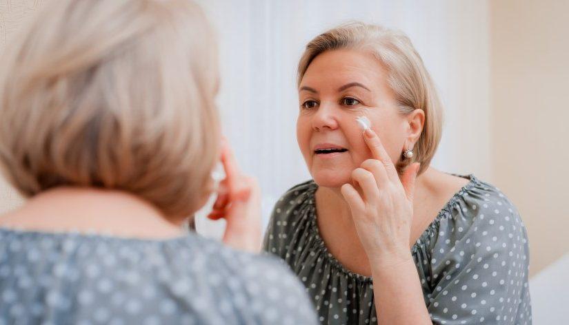 Ældre kvinde der smører sig med creme